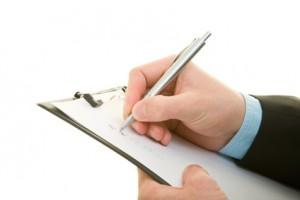 Hand auf einem Klemmbrett hakt eine Checkliste ab